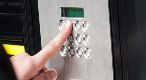 Man entering security code in keypad to unlock door